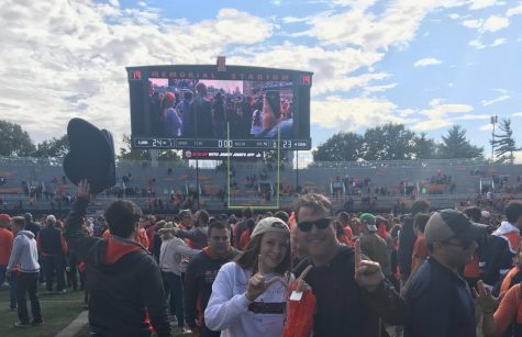 Meghan Lyons and her father celebrate on the field of Memorial Stadium after the historic win against Wisconsin during the Homecoming game Oct. 19. Lyons encourages students to show appreciation for their dads this Dads Weekend.