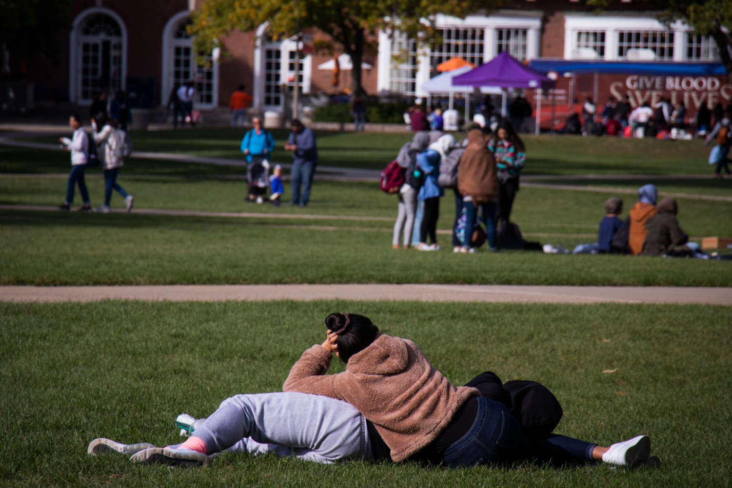 Two students lie on each other on the main quad on Friday afternoon. Columnist Rachel argues that self-love is one of the most important concepts to work toward during the transition to college and the years to follow.