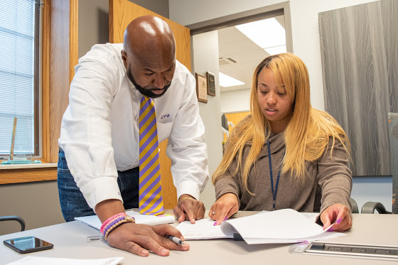 David Northern (left), chief executive officer of the Housing Authority of Champaign County, discusses the new student voucher program that was passed recently with Executive Assistant, Lily Walton (right) on Nov. 14.