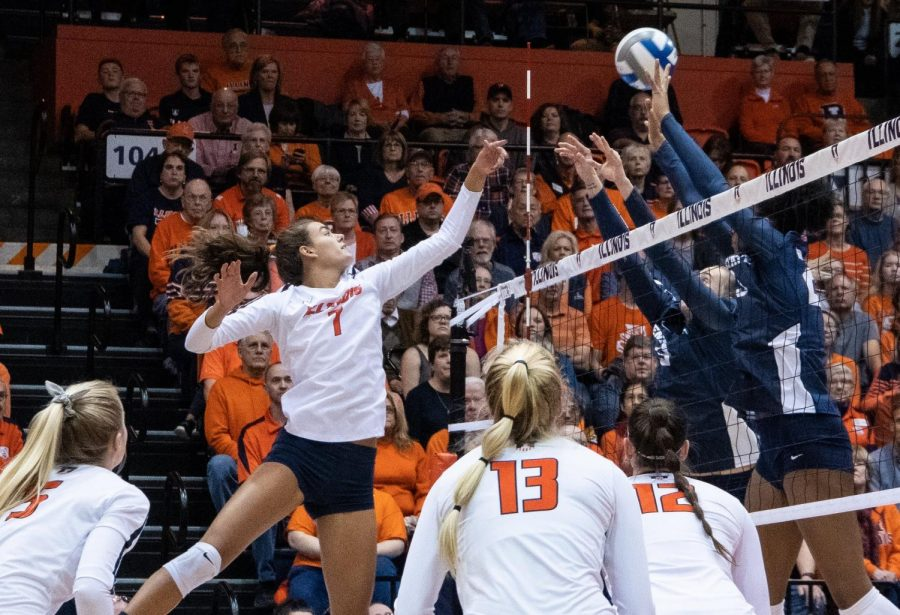 Senior outside hitter Jacqueline Quade spikes the ball against two defenders. Illinois faced Penn State at Huff Hall on Friday.