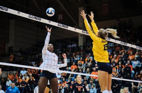 Kennedy Collins sets the ball over a Michigan defender at Huff Hall on Friday.
