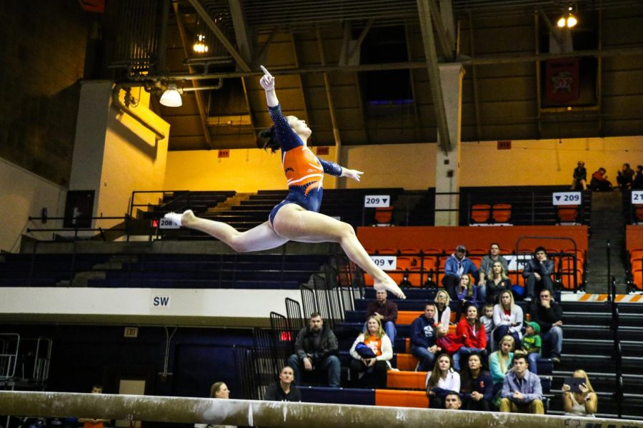 """Kylie Noonan performs on the balance beam at Huff Hall on Saturday. The Illinois women's gymnastics team competed in the Orange & Blue exhibition alongside the men's gymnastics team, where they were split up into """"orange"""" and """"blue"""" squads based on which events the gymnasts competed in; the orange team won 10-9."""