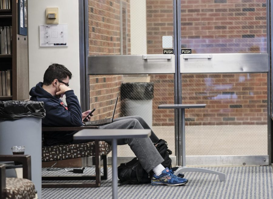 A student sits and stares at his phone on the quiet floor of the UGL on Tuesday. During finals season, some students go to great lengths to procrastinate necessary work.
