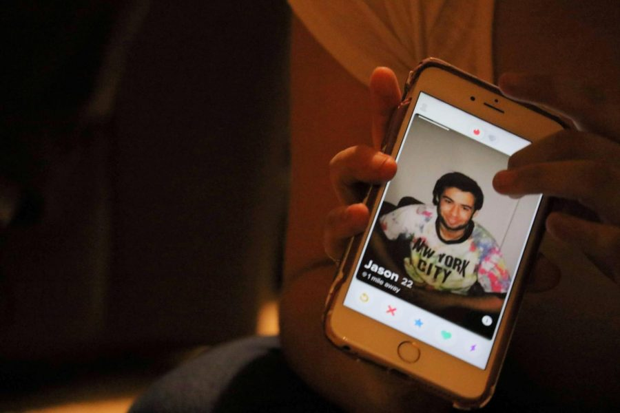 A student holds their phone with the Tinder app open. Returning home after picking up college habits is difficult, especially when it comes to considering the way those vices may impact others.