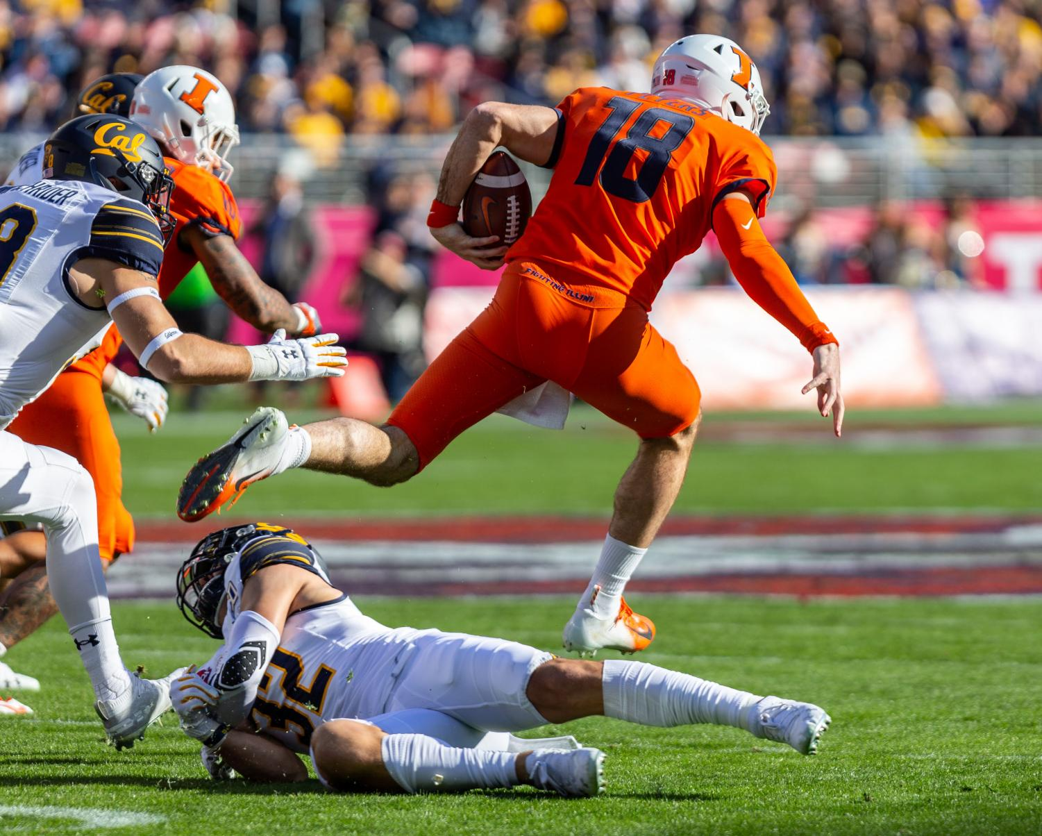 Graudate transfer quarterback Brandon Peters jumps over a California defender during the Redbox Bowl on Monday. Illinois fell to California 35-20 in the team's first bowl game since 2014.