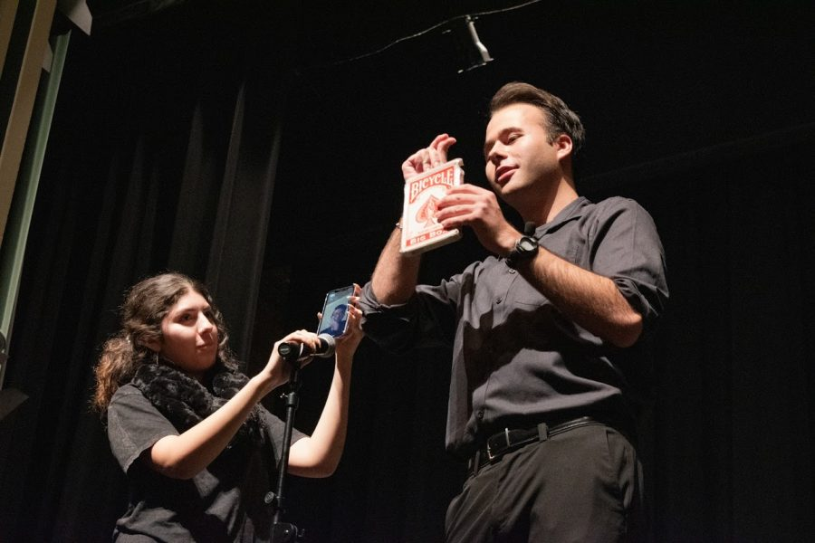 Magician Giancarlo Bemini performs a trick with an audience member's friend through the phone during his performance in Lincoln Hall Thursday. The Scholar Support Programs organize similar events each month to give scholars new experiences.