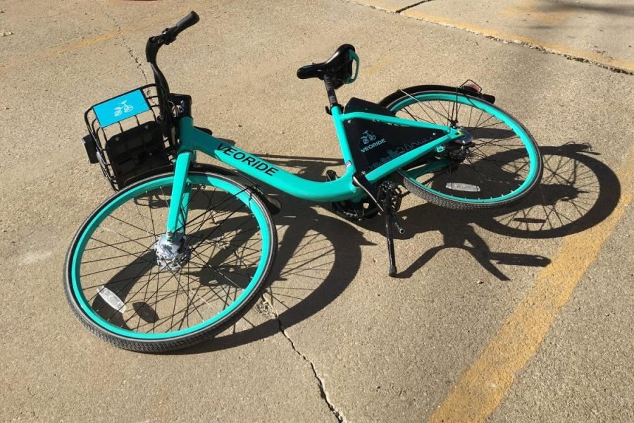 A VeoRide is left tipped over in a residential parking lot on Sixth and Clark streets on Oct. 24, 2018. The e-bikes will most likely relaunch after spring break.