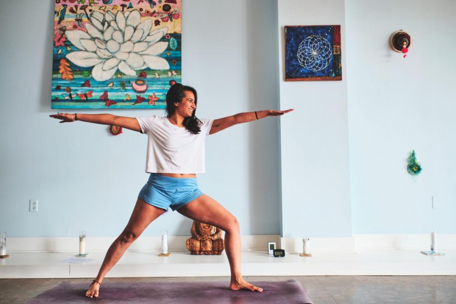 Yoga instructor Tanya Krishnamani performs a warrior two pose before her Vinyasa Flow class at Amara and Arts in Urbana Wednesday. Yoga teacher Genesee Spridco encourages students to empower their mind and body connection through yoga.