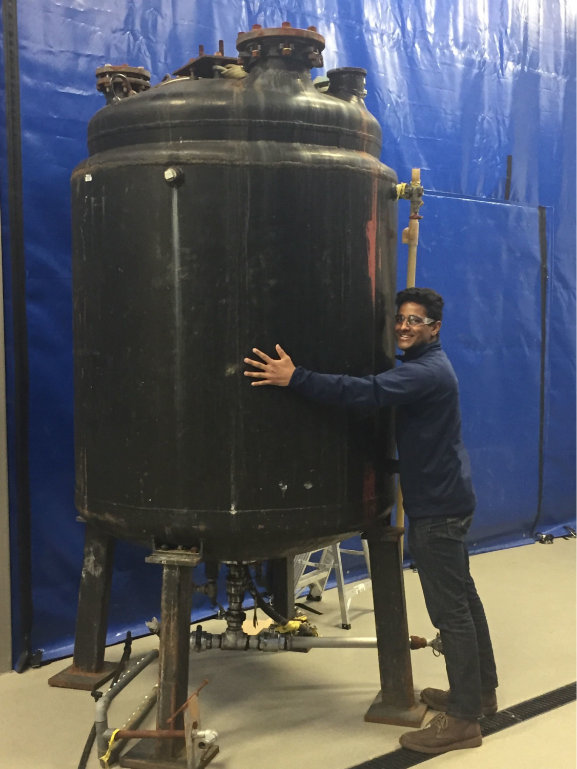 Safety officer Aakash Patel hugs the Illinois Biodiesel Initiative new 500-gallon batch processor. The organization is hoping to make the community more environomentally friendly.