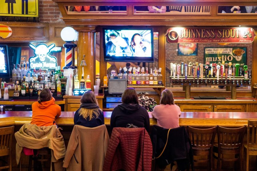 Four students at Brother's Bar watch the Bachelor on March 6.