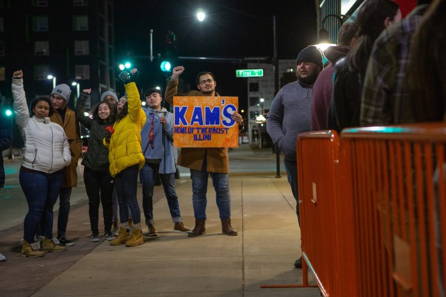 Students raise their fists in protest of Kam's on Thursday night. Kam's workers did not interact with the student protesters.