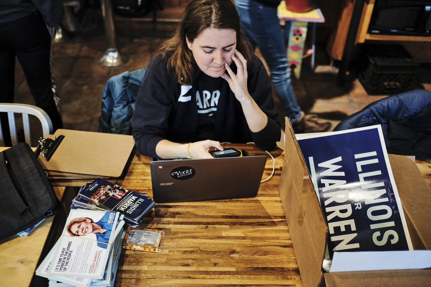 Tori Hill, an organizer for the Warren Campaign, prepares canvassing materials at Caffe Paradiso on Sunday afternoon.