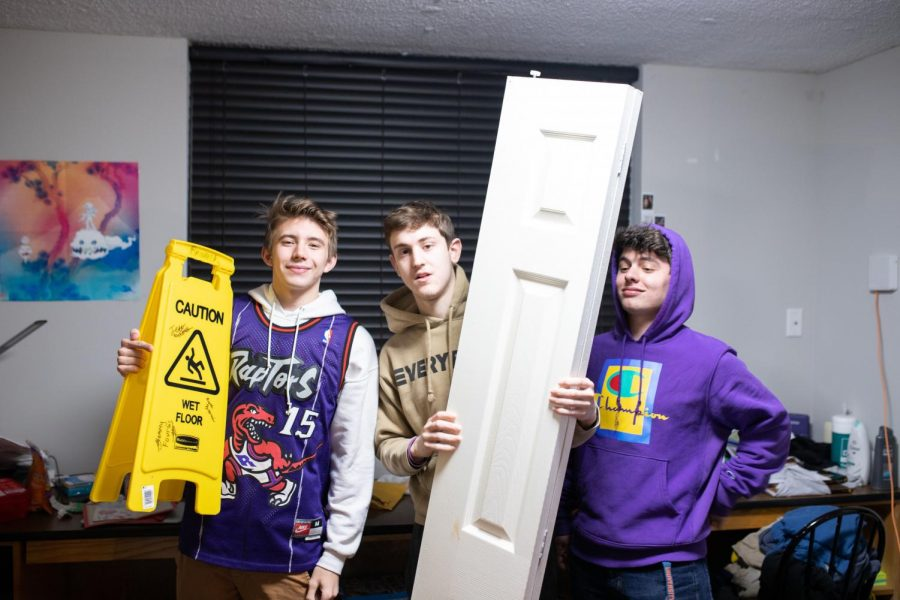 (From left to right) John Koulentes, Sam Fourlas and Ayal Zipris pose with the wet floor sign and closet door from their most viral tik toks. The video using the wet floor sign is at 3.3 million views and the closet door video is closely following at 3.3 million views.
