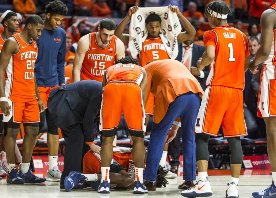 Sophomore+guard+Ayo+Dosunmu+%2811%29+is+attended+to+by+coaches+as+the+Illini+bench+looks+on+late+during+the+second+half+at+State+Farm+Center+on+Tuesday.+Dosunmu+went+down+after+his+knee+buckled+while+driving+toward+the+basket+on+the+final+play+as+the+Illini+lost+to+the+Michigan+State+Spartans+70-69.+