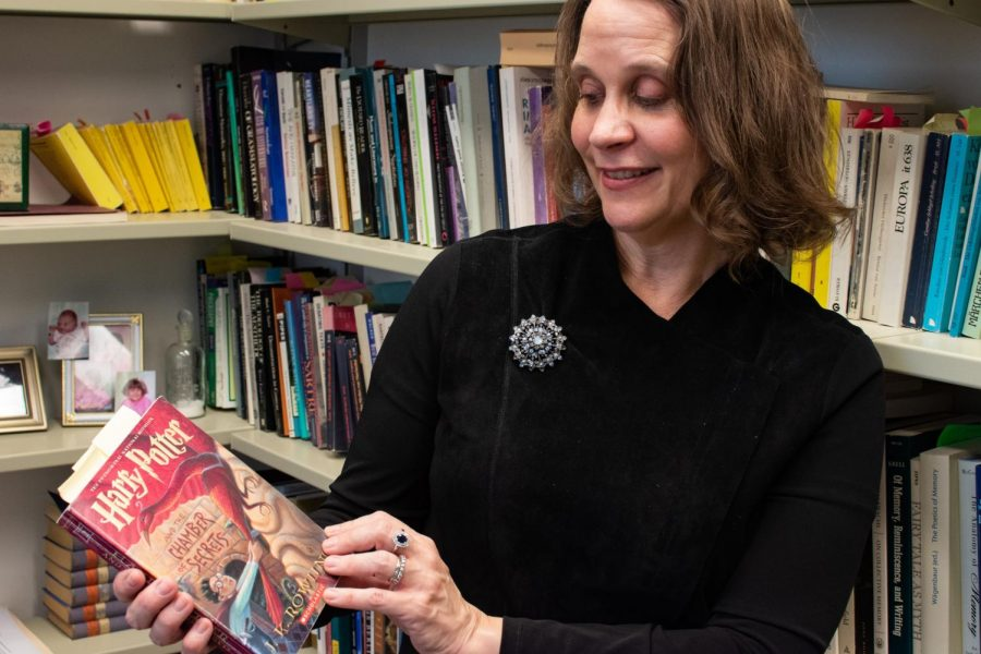 "Laurie Johnson, professor in LAS, poses with ""Harry Potter and the Chamber of Secrets"" Tuesday. She is currently teaching GER 199/CWL 199: Harry Potter and Western Culture."