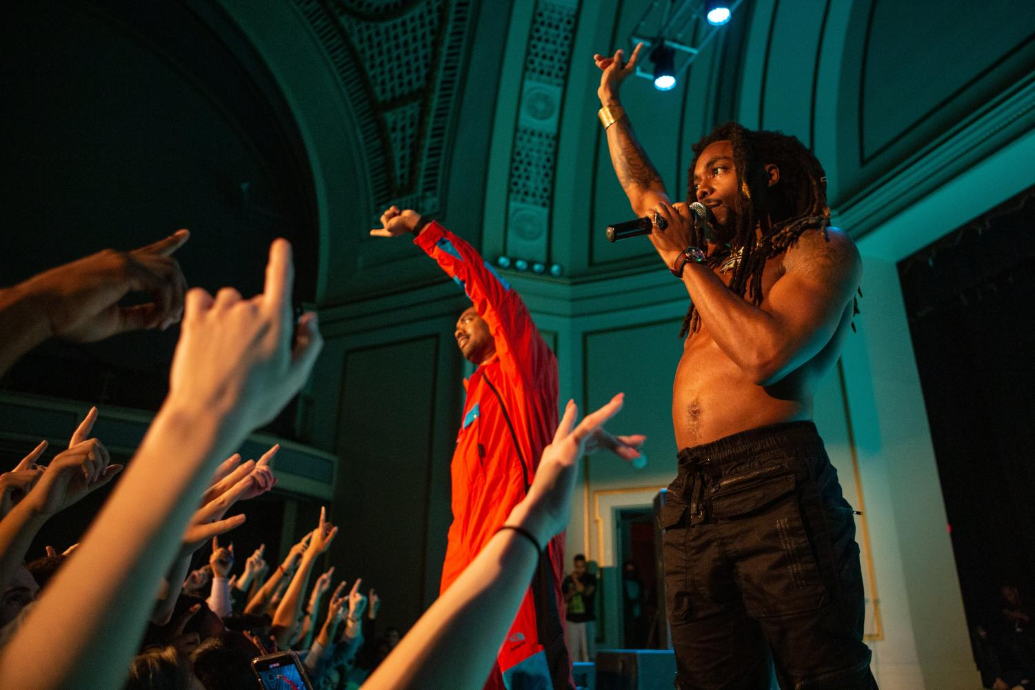 Members+of+EarthGang+raise+their+hands+to+hype+up+the+crowd.