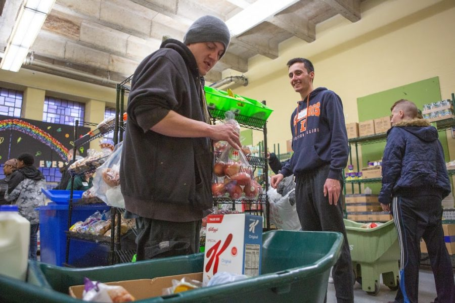 A local man places mangos into his cart as a student volunteer smiles at the Wesley Food Pantry, 1203 W. Green St., on Feb. 20.