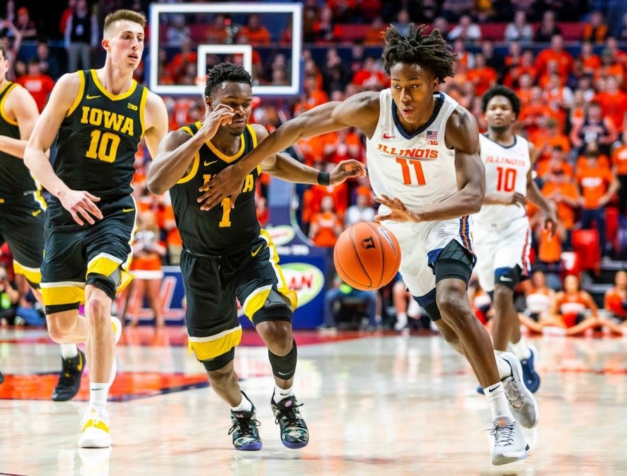 Sophomore guard Ayo Dosunmu speeds around two defenders during the match against Iowa on March 8. The Illini won the match 78-76.