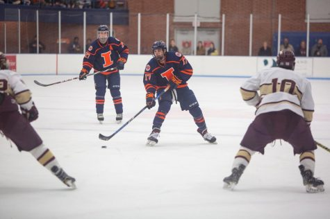 Senior Forward Jon Moskaluk advances the puck down the rink as two defenders move to intercept him during the match against Robert Morris University on Feb. 29