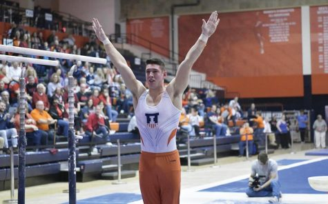Senior Sebastian Quiana raises his hands after performing on the parallel bars at Huff Hall.