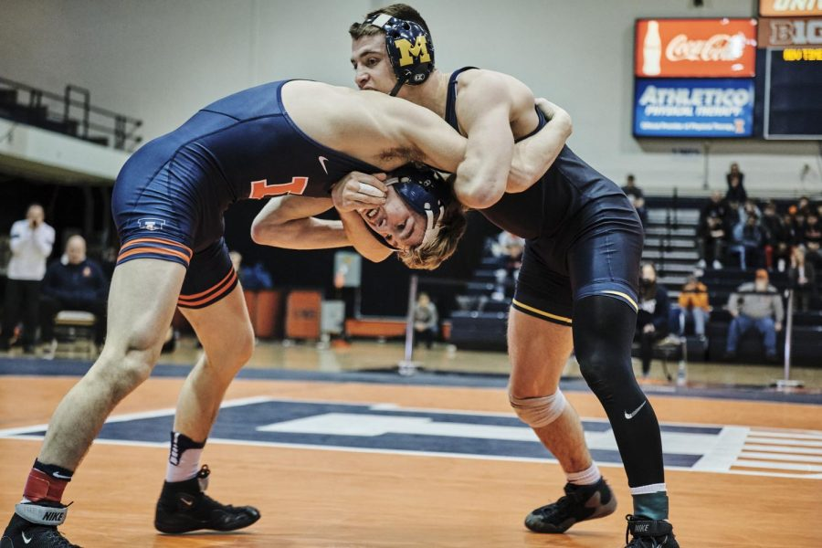 Senior Travis Piotrowski wrestles Austin Assad during the Illinois' dual against Michigan on Jan. 26 at Huff Hall. Six Illini wrestlers qualified for the NCAA Tournament on Sunday.