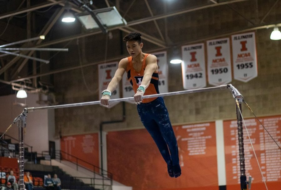 Freshman+Evan+Manivong+competes+in+the+high+bar+event+during+the+meet+against+Penn+State+and+Michigan+on+Saturday.+The+Illini+prevailed+over+the+Wolverines+and+the+Nittany+Lions+with+a+score+of+406.900.%0A
