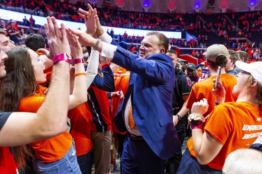 Illinois head coach Brad Underwoos high fives members of the Orange Krush student section after Illinois' game against Iowa at State Farm Center Sunday night. The Illini beat the Hawkeyes 78-76.