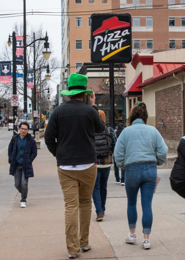 Unofficial participants walk down Green Street past the Pizza Hut on Friday.