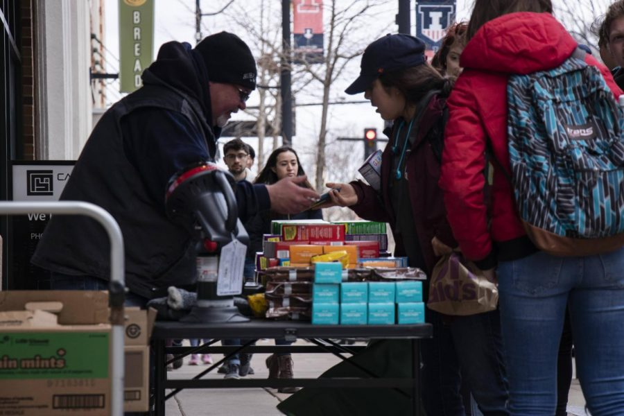 Robert Tuel sells girl scout cookies to students on Green Street during Unofficial on Friday.