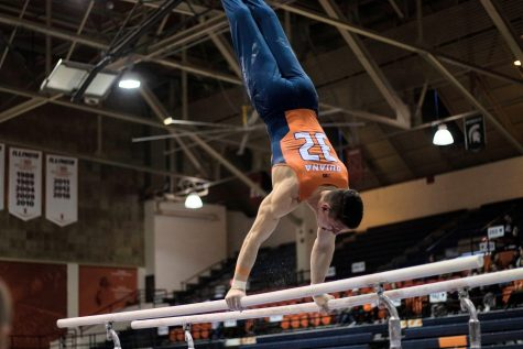 Senior Sebastian Quiana performs on the parallel bars during the Illinois' meet against Penn State at Huff Hall on March 7.