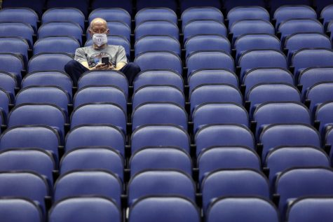 Mike Lemcke, from Richmond, Va., sits in an empty Greensboro Coliseum after the NCAA college basketball games were cancelled at the Atlantic Coast Conference tournament in Greensboro, N.C., Thursday, March 12, 2020.