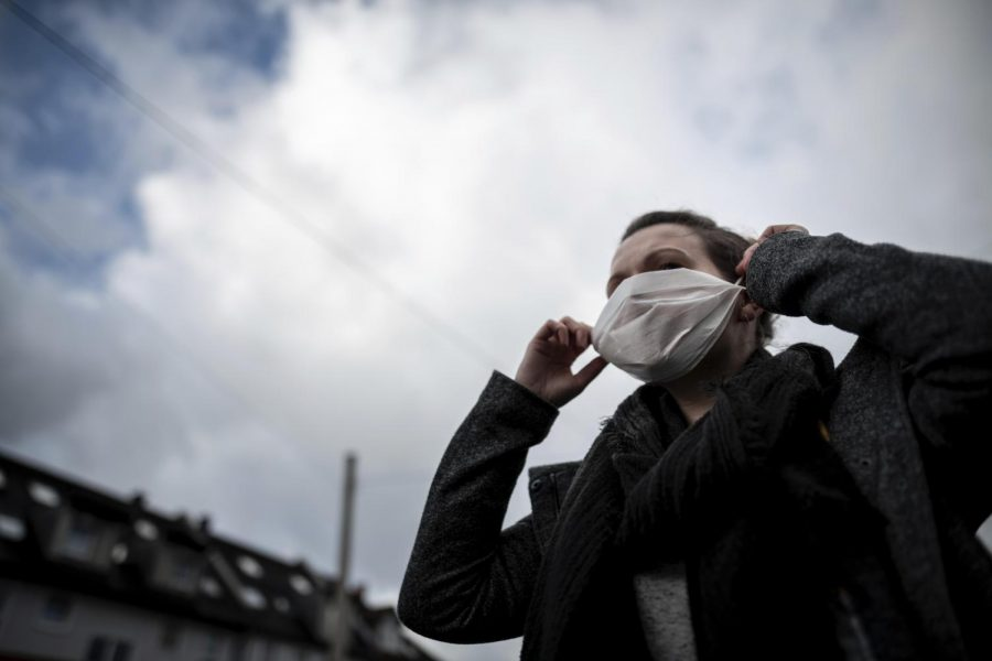 A woman wears a mouth and nose mask in front of a pharmacy. The first case of the corona virus in Germany has greatly increased the demand for breathing masks in pharmacies.