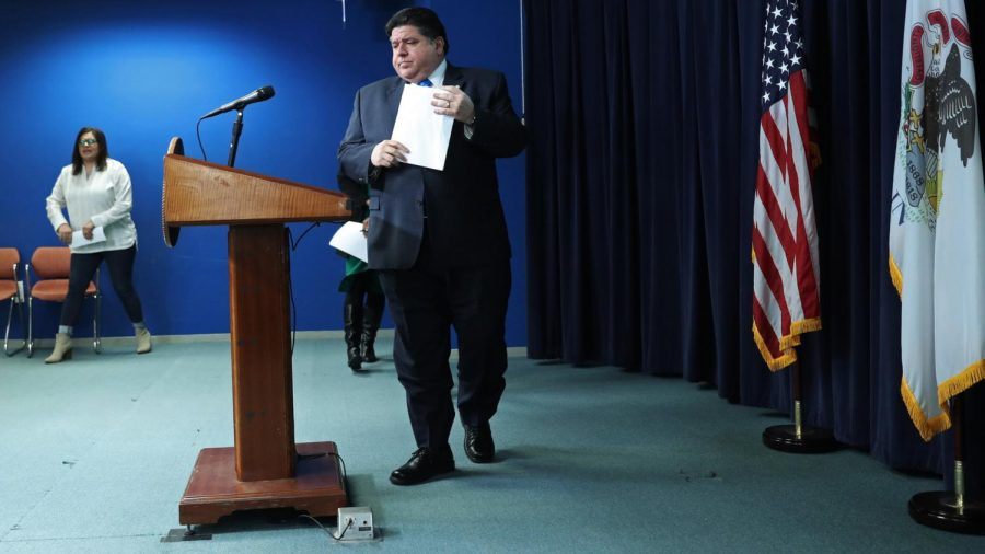 Gov. J.B. Pritzker approaches a podium to brief news media on the most recent Illinois COVID-19, or coronavirus, numbers and statistics, and issues surrounding suppression efforts, at the Thompson Center Tuesday, March 17, 2020, in Chicago.
