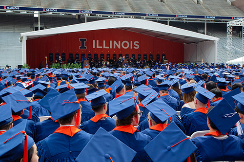 Graduating students wait to walk across the stage and receive their diplomas during commencement in 2018 at Memorial Stadium.