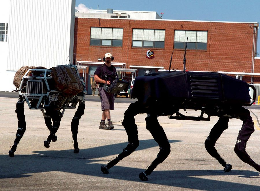 BigDog robots trot around in the shadow of an MV-22 Osprey while given commands via remote control at Marine Corps Air Station New River, N.C., June 26, 2006.
