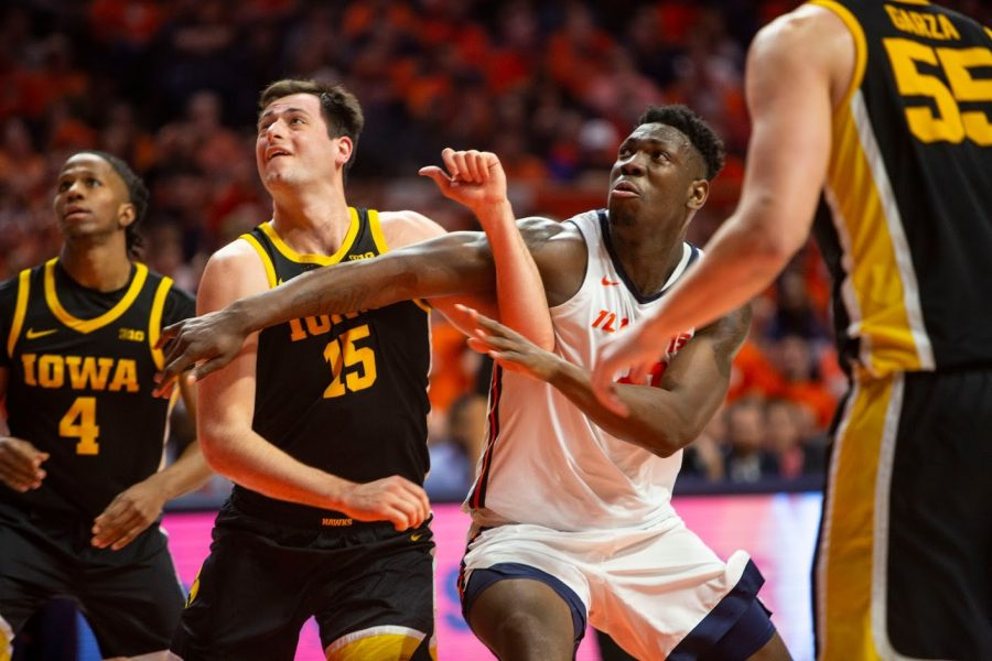 Freshman Center Kofi Cockburn jockeys with Iowa Forward Ryan Kriener for position under the basket during the match against Iowa on March 8. The Illini won the match 78-76.