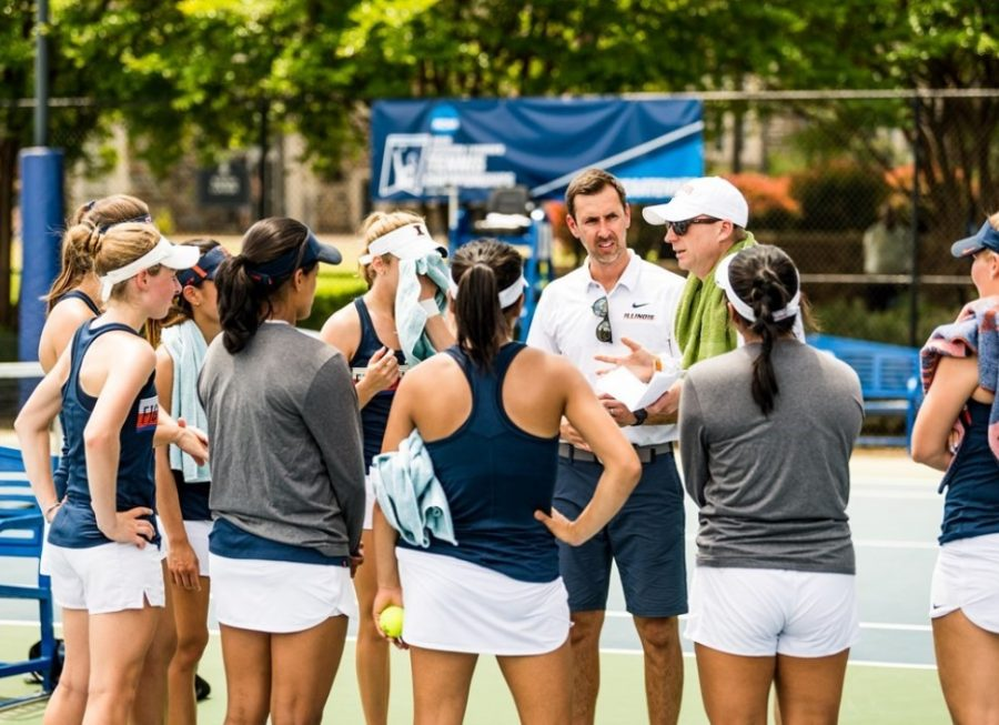 Illinois Women's Tennis Head Coach Evan Clark, wearing a white hat and sunglasses, huddles with his team before matches begin during a meet against Arizona State on May 4, 2019.
