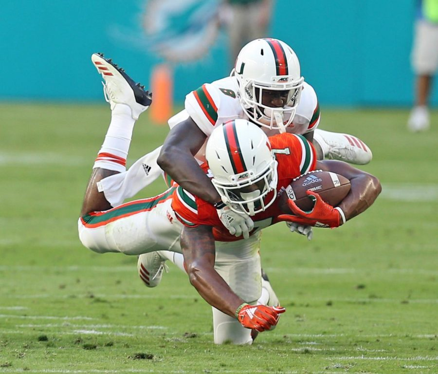 Miami's Brian Hightower catches a pass as D.J. Ivey, top, defends in the second quarter of the Hurricanes' spring scrimmage at Hard Rock Stadium in Miami Gardens, Fla., on Saturday, April 14, 2018.