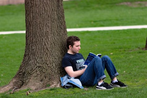 An Illinois student reads a book while leaning against a tree on the main quad on April 3.