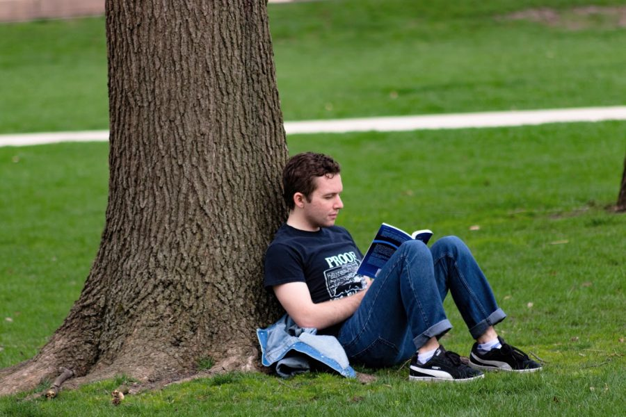 An+Illinois+student+reads+a+book+while+leaning+against+a+tree+on+the+main+quad+on+April+3.+