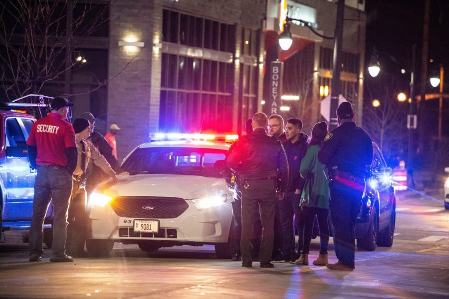 Police confront a man and issue a drinking ticket during Unofficial on Mar. 1, 2019.