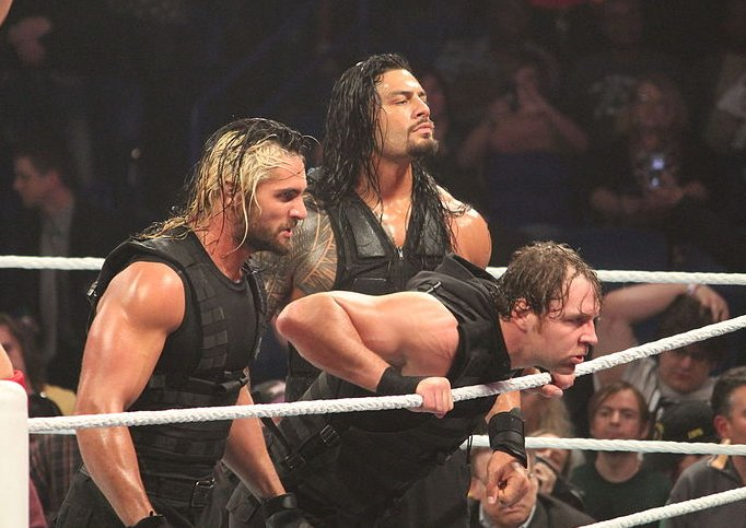 Three WWE wrestlers look out towards the crowd from inside the ring during a WWE event on April 7, 2014.