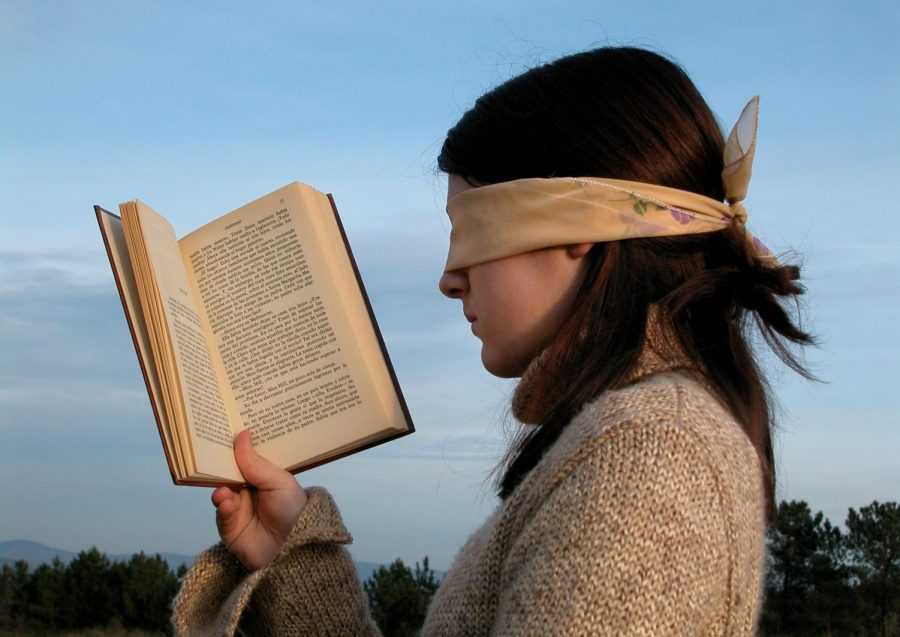 A woman wearing a blindfold holds a book in front of her.
