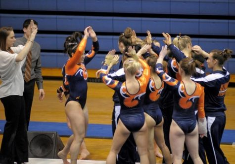 The Illinois Women's Gymnastics team celebrates after one of its members completes their routine during a match against Michigan on Feb. 7, 2014.