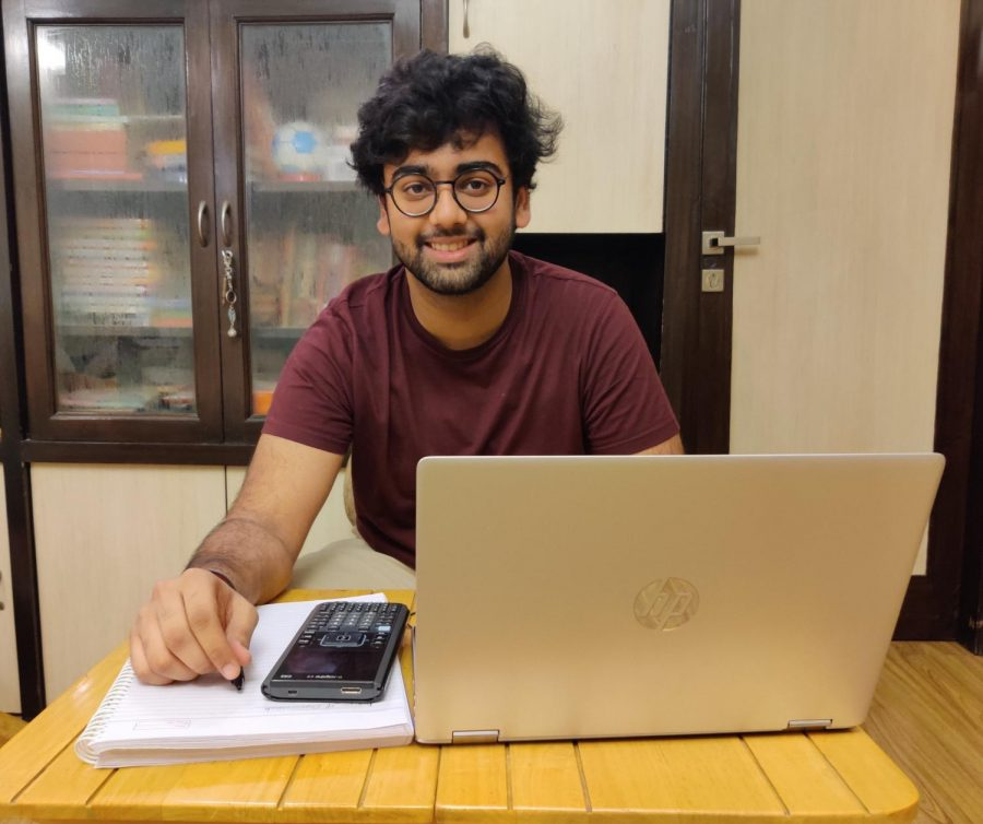 Junior Vishrut Khaitan sits at a desk with the materials he needs to do school work.