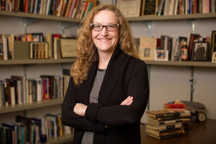 Professor Cara Finnegan poses for a photo in her office