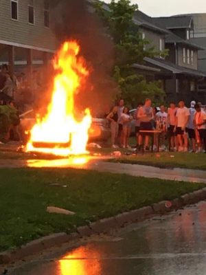 Students watch as a couch goes up in flames in Champaign on May 16.