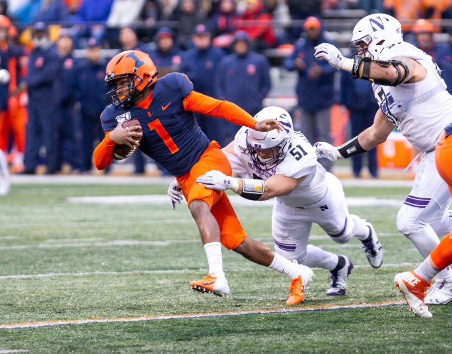 Illinois+Quarterback+Isaiah+Williams+slips+through+a+defender%27s+tackle+during+the+match+against+Northwestern+on+Nov.+30%2C+2019.