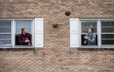 Two college students make the most of quarantine by tossing a basketball back and forth through open windows on April 18, 2020 in Susquehanna, Pennsylvania.