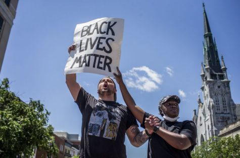 Two protesters hold a sign above their heads during a Black Lives Matter Demonstration  in Harrisburg, PA on Saturday.